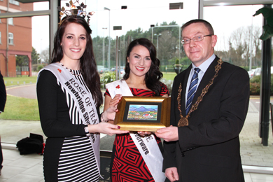 Rose of Tralee Nicola McEvoy, left, on a visit to the Slieve Donard Resort and Spa in Newcastle receives a presentation of a painting from Down District Council Chairman Councillor Mickey Coogan. Included is the current Down Rose, Una Matthews.