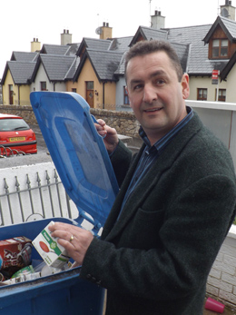 Councillor Willie Clarke pops a tetra pack into the blue bin.