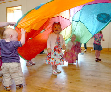 Young children enjoying the parachute at a Sign2Music session.