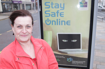PCSP Chairperson Councillor Carmel O'Boyle pictured beside one of the big posters in Newcastle.