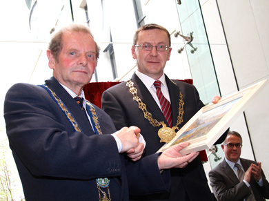 Newry and Mourne District Council MAyor Councillor John McArdle presents a gift to Down District Council Chairman Councillor Mickey Coogan.