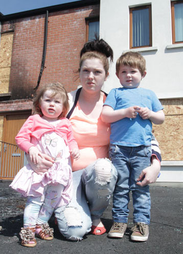 Contemplating the future. Jade McCaul with her two children outside her fire damaged home in Downpatrick.