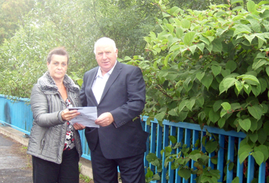 Councillor Carmel O'Boyle, Chair of the xxx Committeeand desmond Patterson, Chaor o fteh Estates Committee, look over the Japanese Knotweed invading the river at Bryansford.