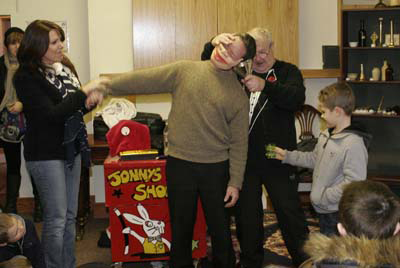 Brain surgery at the Down County Museum as magician Jonny extracts blood from another John's ear after 'keyhole'  surgery accompanied by two able assistants. (2010).