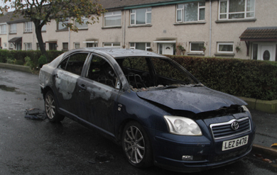 A dark blue Toyota Avensis burned out with windows smashed lies in Burrendale Park Close after the early morning row.