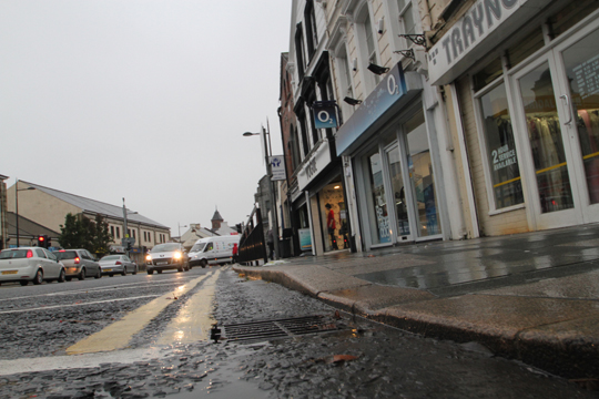 Downpatrick's Lower Market Street traders may eventually be free from occasional flooding if the proposed sewerage measures by the DRD are effective .