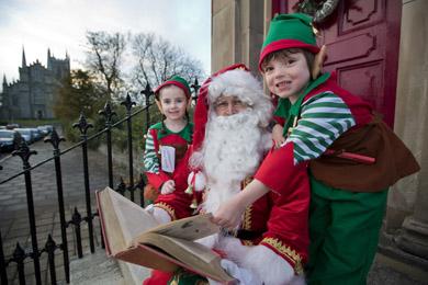 Santa's elves Aleesha Douglas and Louis Scullion both from Downpatrick. aged 5 with Santa checking out his Christmas diary.