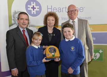 Sports Minister Carál Ni Chuilín and Declan O'Mahoney, Chief Executive of defibrillator manufacturer, HeartSine Technologies pictured with Ella Denver and Shea Dorian with St Nicholas' Primary School principal Eamon Fitzsimons.