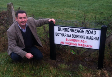 Cllr Clarke pictured at the new bilingual street sign which has been installed in Burrenreagh.