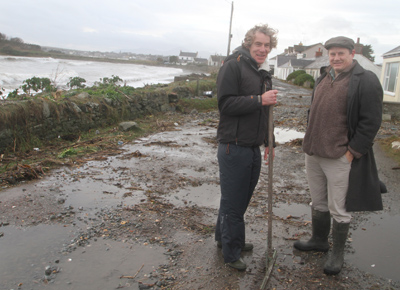 Coney Islander Kevin Lappin clears up after the tidal flood at Coney Island and chats to Down Councillor Cadogan Enright.