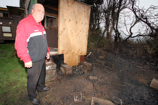 Clifford Healy from KIllyleagh looks over the charred remains of his pigeon loft destroyed in an arson attack.