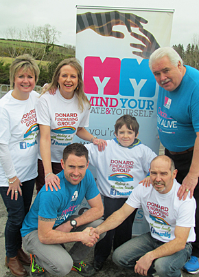 Donard Fundraising Group Chairman Paul Madden (front, right) volunteers Kate Pell, and Jacqui Mason and young helper Raphael Madden, welcome the news that the group, as well as continuing their support for Marie Curie Cancer Care, will also be lending their support to the local Mind Your Mate & Yourself (MYMY) organisation, represented here by Raymond Cunningham and Danny Wallace.