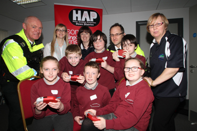 Neighbourhood Policing Sergeant John McKenna, Kelly Squance, HAP Chairperson, Heather Holland, County Down RCN Community Health Woprker, Constable Philip Orr and Jenny Laverty, Flying HOrse ward CommunityForum Health Worker with pupils from St Joseph's PS, Ballycruttle.