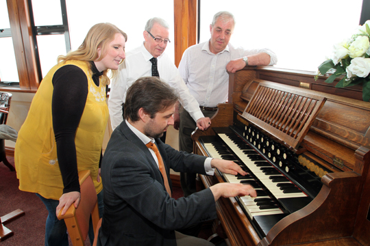 Practising the 1930 Mason and Hanlon harmonium at Down Funeral Directors in Downpatrick for The Down Chorus is Nicholas Boyle, Musical Director of The Down Chorus. Looking on are Aisling Clarke, Artistic Director, with funeral directors Louis Deegan and Patsy Fitzsimons.