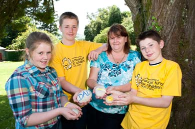 Newry family Chloe, Ryan, Barbara, and Keith Doran holding pebbles with their personal messages written on them. The Doran's have received support from Cancer Fund for Children. This year, participants of the Slieve Donard climb will be invited to write their own messages on a pebble and leave it at the top of the mountain. Funds from this year's event will help the charity provide practical, emotional and financial support to local families affected by cancer.