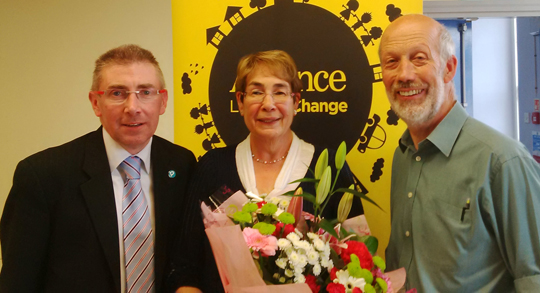 (Councillor Patrick Clarke) and Alliance Leader David Ford taken on Saturday in Newcastle Centre presenting South Down Alliance Secretary Mary Smyth Farr with a bouquet of flowers in recognition of her 44 years service to South Down Alliance since the Alliance party was first founded in 1970.