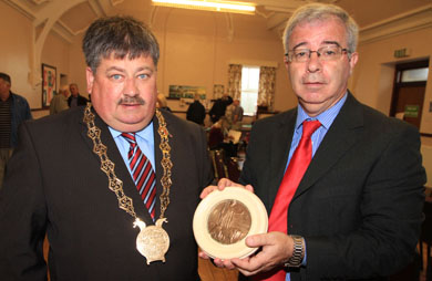Former Down District Council Chairman Cllr William Walker with a death penny from his namesake William Walker from World War One, and event organiser Chris Hagan.