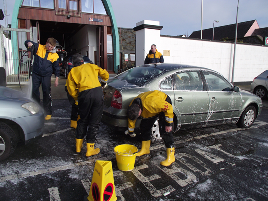 Volunteer crew members from the Portaferry RNLI Lifeboat Station clean cars to help raise money for the RNLI