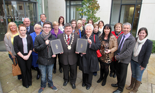 Members of the County Down RCN and the Downpatrick Community Collective receive a recognition from Down District Council Chairman Cllr Billy Walker for their success in the Cooperation Ireland Pride of Place Awards.