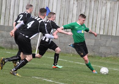 Karal Jaroinski making a cross for Castlewellan under pressure from Newcastle defenders.