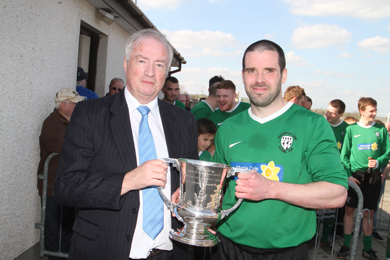 Robert Hayworth, chairman of the Newcastle and District Amateur Football League, presents the Harry Clarke Cup to Conor Stratton, Castlewellan captain.