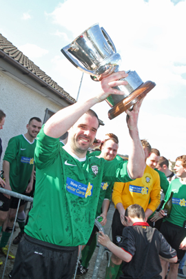 Castlewellan FC captain Conor Stratton holds up the Harry Clarke Cup.
