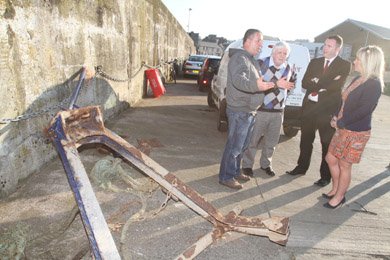 Skipper Paul Murphy, NIFPO chief executive Dick James, Chris Hazzard MLA, and Fisheries Minister Michelle O'Neill look over part of a steel support ripped off the deck of the Karen as the submarine snagged the wires to her net.