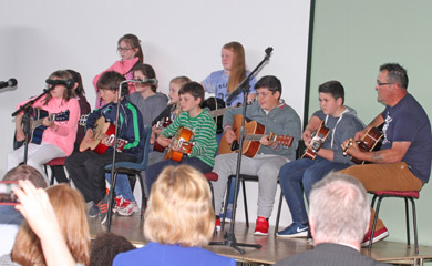Children from Annsborough show off their skills on the guitar.