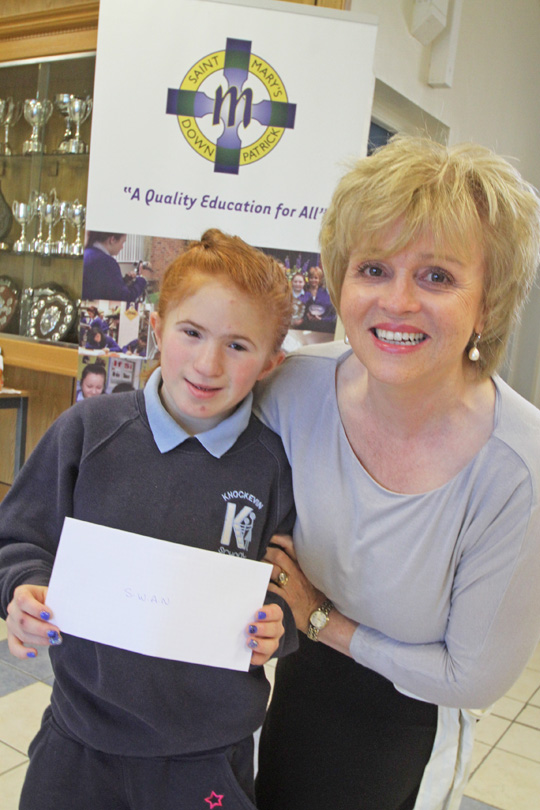 Young Caoimhe Rhodes-McMenamin, a Knockevin School pupil, receives a cheque for her chosen charity, SWAN, from St Mary's High School principal Mrs Sheila Darling.