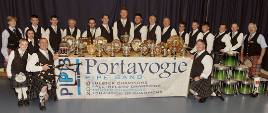 Portavogie Pipe Band pictured with their array of trophies at a celebratory dinner in Portavogie Community Centre on Saturday 26th September.  Included are Pipe Major Malcolm Wallace (left of trophies), Drum Sergeant Winston Murdock (right of trophies) and Royal Scottish Pipe Band Association guests Arlene Graham, RSPBANI Vice-Chairman (left in back row) and Kenny Crothers, RSPBA Director (right in back row).