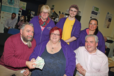 Gabriel Magee presents the runner up prize of £50 to CAPAA chair Moira Denvir. Included are CAPAA members Tina McManus, Conor McCambridge,   and Joan Fitzpatrick with Hub Manager Stephen McClelland.