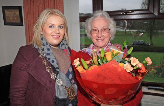 Newry Mourne and Down Down District Council Chairperson Cllr Naomi Bailie presents a bouquet of flowers to Enda Calvert  from Roughal Park in Downpatrick who was burgled.