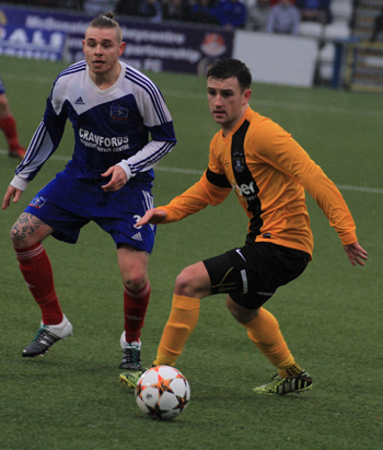 Albery Foundry defender darryl McAlinden challenges Welders player Chris Middleton in possession.