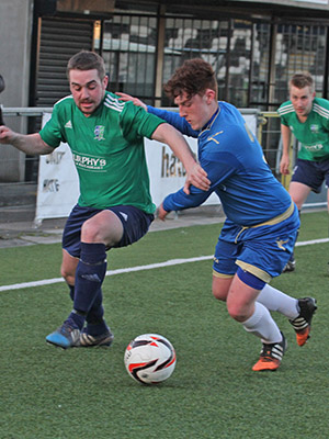 Downpatrick's top goal scorer Stephen Galbraith presses down the right wing and is challenged by Lisburn Rangers defender George Douglas.