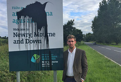 Alliance Councillor Patrick Brown is concerned about the defacing of Council signs. He is pictured above at the latest one painted over at Ballygowan.