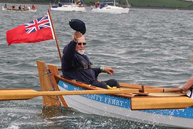 A coxswain give a wave from the Brought Ferry skiff as it rows its way from Delamont Country Park  round STrangford Lough to Strangford harbour.