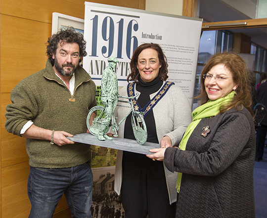 Barry Linnane presents a maquette of the artwork to Councillor Gillian Fitzpatrick, Chairperson of Newry Mourne and Down  District Council and Noreen Cunningham, Curator, Newry and Mourne Museum.