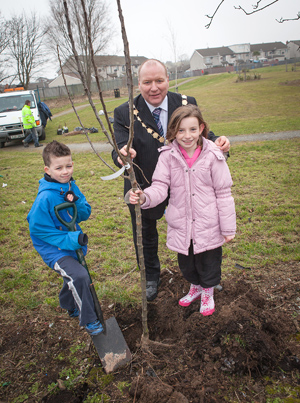Alderman Hamilton Gregory, Mayor of Ards, with local Ballygowan schoolchildren Michael Coomber and Rachel Gourley plant a fruit tree.