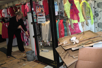 Staff in Vogue fashion shop mop up after the flood abated.
