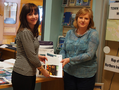 Sinead Maguire from the First Flight Wind Community Liaison Team delivers copies of the 'Round One Summary Report' to Pamela Houston, Chief Executive of the Kilkeel Development Association who own and operate the Nautilus Centre at Kilkeel Harbour. The Nautilus Centre is one of First Flight Wind's Information Points.