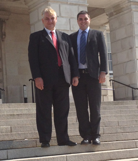 Councillor Henry Reilly and representative Alan Lewis on the steps of Stormont.