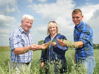 Minister Michelle O'Neill is pictured with irganic farmer John Carson and son  Jonathan on his farm in Downpatrick.