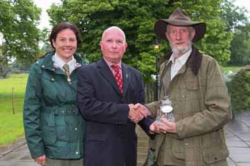Rademon gamekeeper Hayley Dobbin adds her congratulations as Paul Pringle (centre) presents her predecessor Robin Magee  with an Award from The Great Game Fairs.