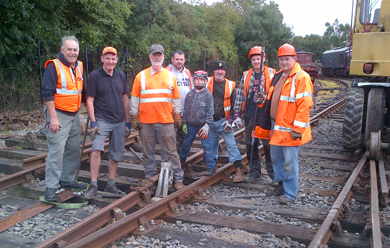 Photograph with David Crone Front Centre, Barry Mervyn back centre and Cllr Councillor Cadogan Enright, right, at a new track installation in the station yard with a group of volunteers.