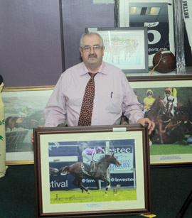 Downpatrick-based Turf Club official, Frankie Fitzsimmons pictured with some of auction items in aid of the Jonjo Bright Trust Fund and holding the picture of Camelot winning the Epsom Derby signed by Joseph and Aidan O'Brien.