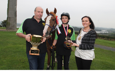 Jacob Morrow (13) from Killyleagh, centre, the Home International Junior Champion, with David Cunningham, manger of the Irish Long Distance Riding Association team holding the Home International Cup, and Down District Council Chairman, Cllr Maria McCarthy.