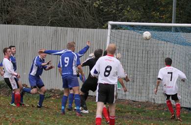 KIlmore's Johnny Cheevers hits the bar with a header.