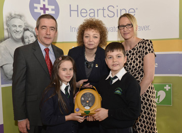 Declan O'Mahoney, Chief Executive of defibrillator manufacturer, HeartSine Technologies and Sports Minister Carál Ni Chuilín with St Macartan's PS pupils from Loughinisland Lauren Gregg and Jimmy McLeigh with teacher Angela Murray.