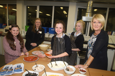 Erin Belshaw, St Patrick's Primary School, Ballynahinch, in the Domestic Science room getting a pizza made up. Also pictured are Blackwater pupils Lucy Fitzpatick, Grace Stewart, Tara Armstrong with Teaching Assistant, Aisleain Reynolds.