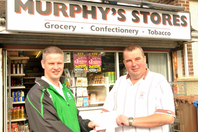 Tony McShane of Downpatroick FC receives a match sponsorship cheque from Mark McMurphy of  Murphy's Stores.